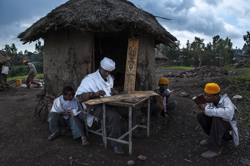 Poster A priest is painting while some guys are praying (Lalibela - Ethiopia)